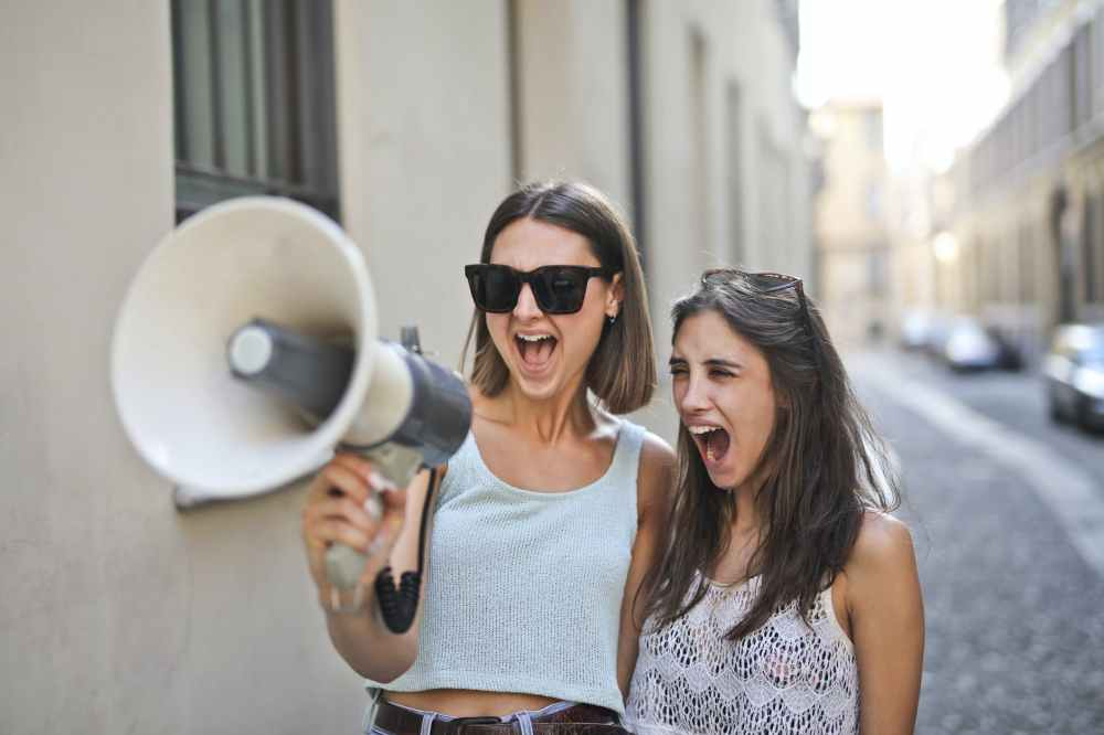 cheerful young women screaming into loudspeaker